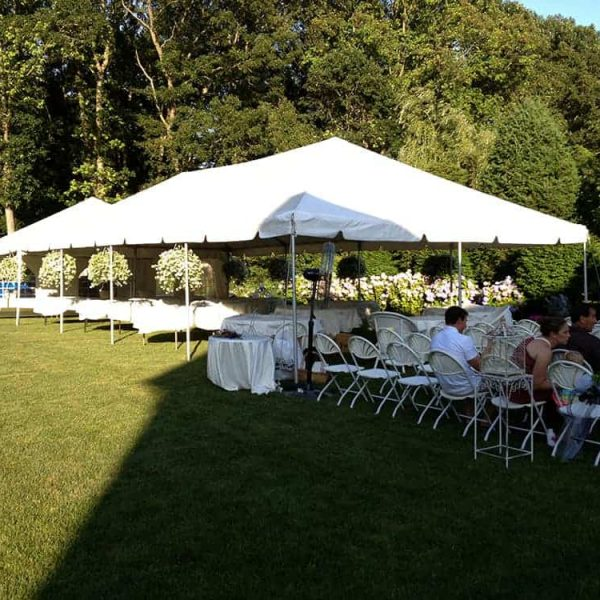 grass setup of tent rental with chairs